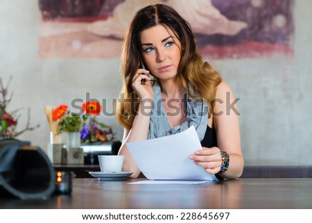 Young woman on the phone in a cafe or restaurant, she discusses some documents - stock photo
