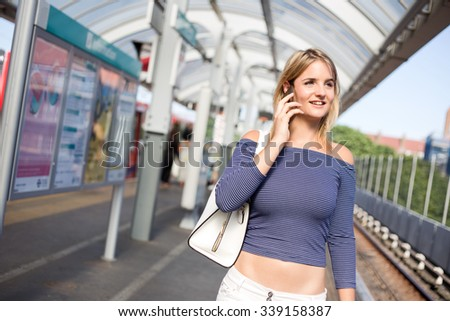 young woman on the train platform using her phone - stock photo