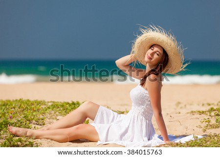Young woman on the tropical beach near the ocean - stock photo