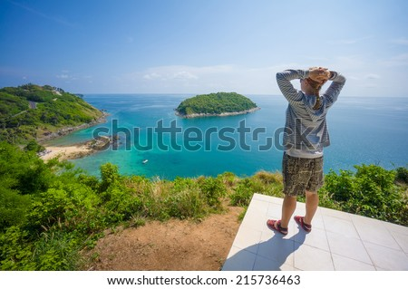 Young woman on tropical island cliff with small beach below - stock photo