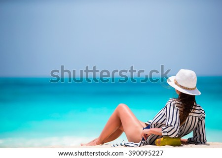 Young woman on white beach with coconut - stock photo