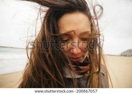 young woman on windy beach, Bosa, Sardinia, Italy - stock photo