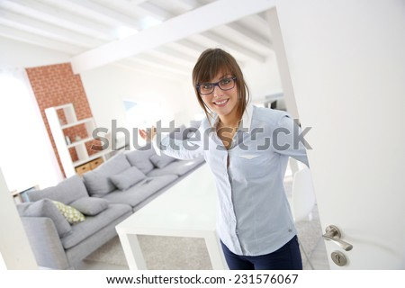 Young woman opening entrance door of new home - stock photo