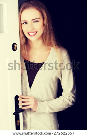 Young woman opening her house door - stock photo