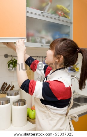 young woman opening the door of kitchen counter - stock photo