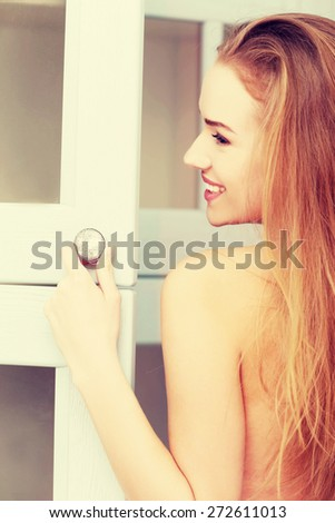 Young woman opening wardrobe doors - stock photo