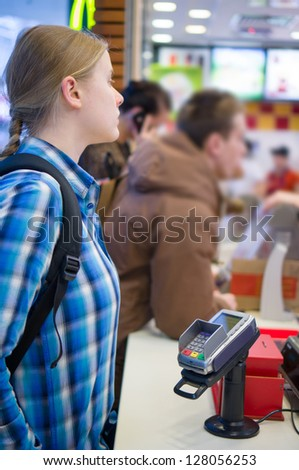 Young woman order meal in fast food restaurant - stock photo
