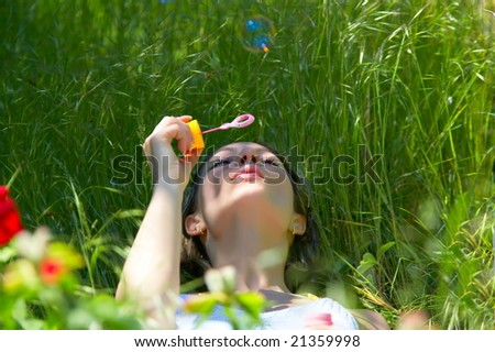 young woman outdoor blowing soap balloons - stock photo