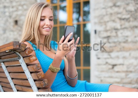 Young woman outdoors texting on her mobile phone and smiling, dressed in blue dress. - stock photo