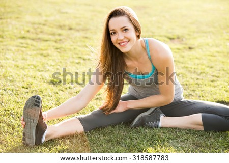 Young woman outside stretching after her workout - stock photo