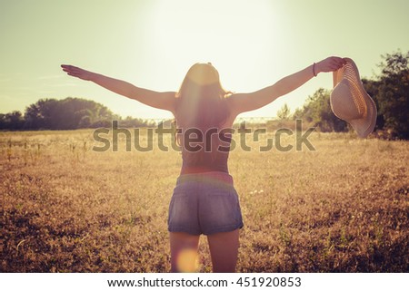Young woman outstretched arms enjoys sunset - stock photo