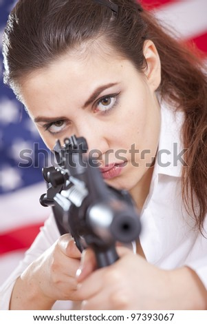 young woman over american flag aiming with machine gun - stock photo