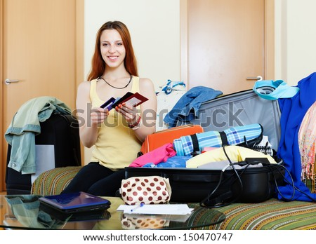 Young woman packing documents into suitcases going on holiday - stock photo