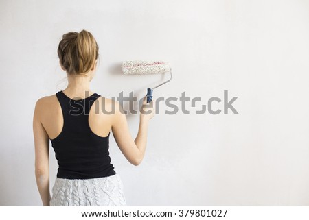 Young woman paint wall - stock photo