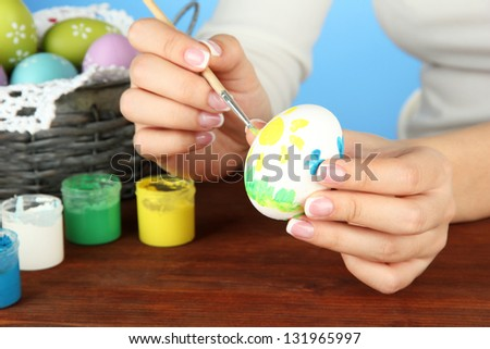 Young woman painting Easter eggs, on color background - stock photo