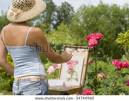 Young woman painting roses in the garden - stock photo