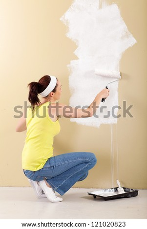 young woman painting the wall in her new home - stock photo