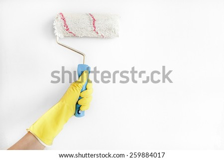 Young woman painting wall with roller brush. - stock photo