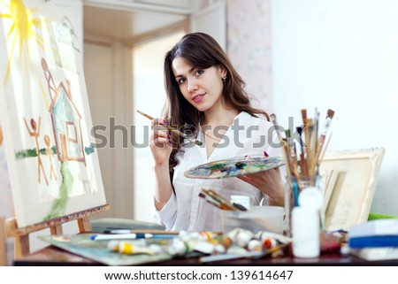 Young woman paints home of dreams on canvas in workshop - stock photo