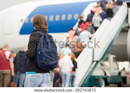 Young woman passenger in 20s travelling with backpack, boarding airplane, people climbing ramp on background, rear view - stock photo