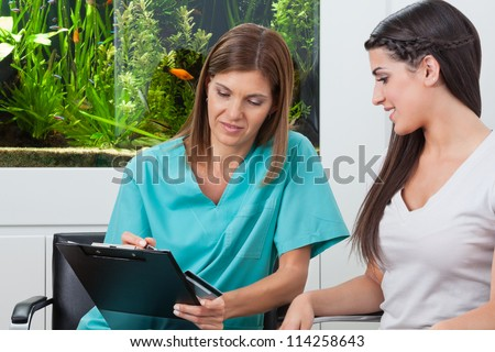 Young woman paying bill through credit card to female dentist in clinic - stock photo