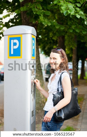 Young woman paying for parking in the street - stock photo