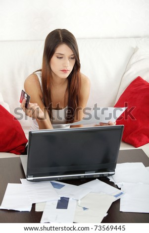 Young woman paying high bills online with credit card. - stock photo