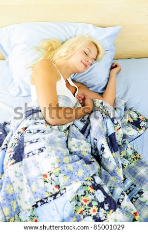Young woman peacefully asleep in bed in the morning - stock photo