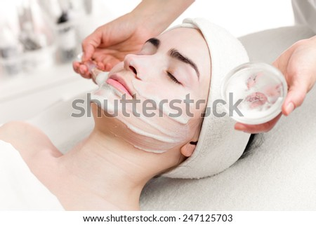 Young woman peeling foam mask applying on face - stock photo