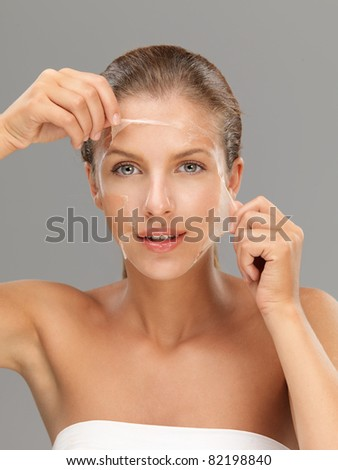 young woman peeling off a facial mask - stock photo