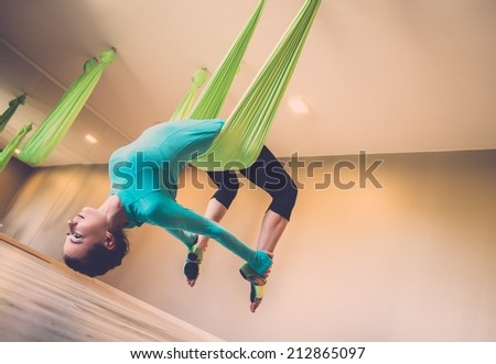 Young woman performing antigravity yoga exercise  - stock photo