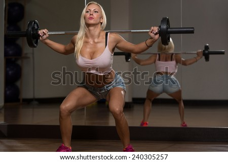 Young Woman Performing Barbell Squats - One Of The Best Body Building Exercise For Legs - stock photo
