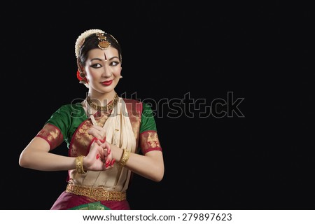 Young woman performing Bharatanatyam over black background - stock photo
