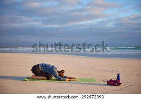 Young woman performing the child yoga pose on the beach on her yoga mat with morning sun shining on her - stock photo