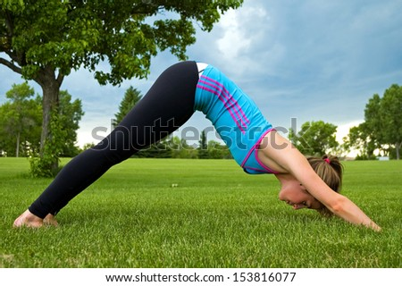 Young woman performing the Down Dog yoga pose, in a park. - stock photo