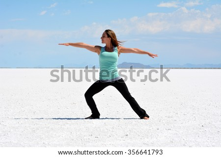 Young woman performing warrior yoga pose on the Bonneville Salt Flats in Utah. - stock photo