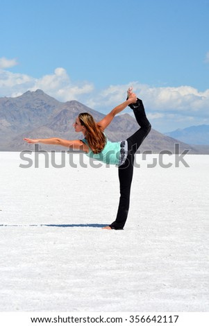 Young woman performing yoga pose at the Bonneville Salt Flats in Utah. - stock photo
