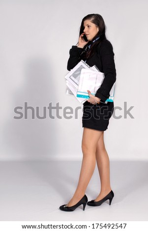 Young woman phone while walking and holding hands a pile of documents - stock photo