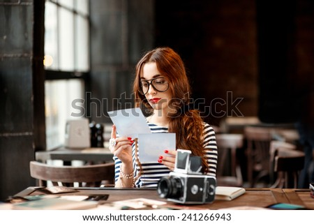 Young woman photographer looking at the printed photos with old 6x6 frame camera sitting in the loft design interior - stock photo