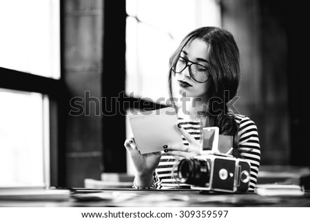 Young woman photographer looking at the printed photos with old 6x6 frame camera sitting in the loft design interior. Black and white photo - stock photo