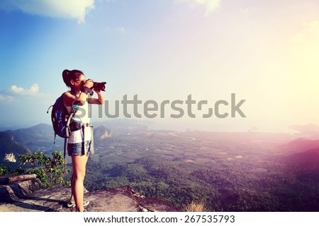 young woman photographer taking photo at mountain peak - stock photo
