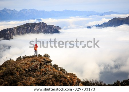 young woman photographer taking photo for beautiful landscape on mountain peak - stock photo