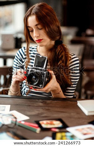 Young woman photographer with old 6x6 frame camera sitting in the cafe - stock photo