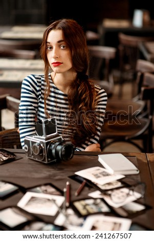 Young woman photographer with printed photos and old 6x6 frame camera sitting in the cafe - stock photo