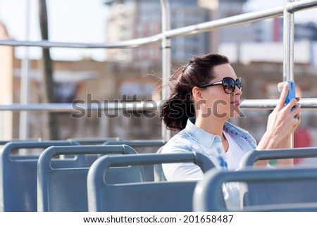 young woman photographing the city using smart phone from an open top bus - stock photo