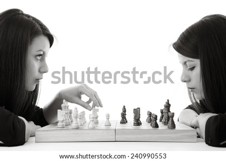 young woman playing chess against herself shot in the studio - stock photo
