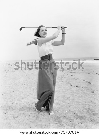 Young woman playing golf at the beach - stock photo