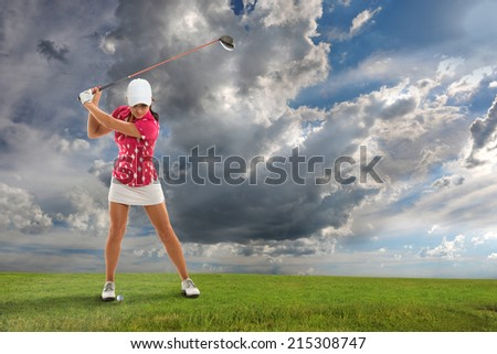 Young woman playing golf on course - stock photo
