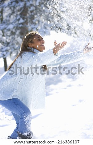 Young woman playing in the snow - stock photo