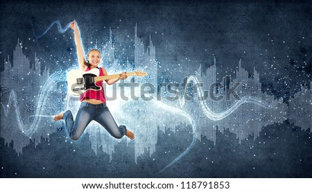 young woman playing on electro guitar and jumping - stock photo